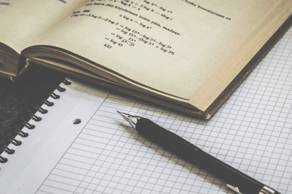 a book beside a grid paper and a pen