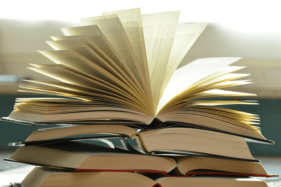 a stack of books with an open on at the top