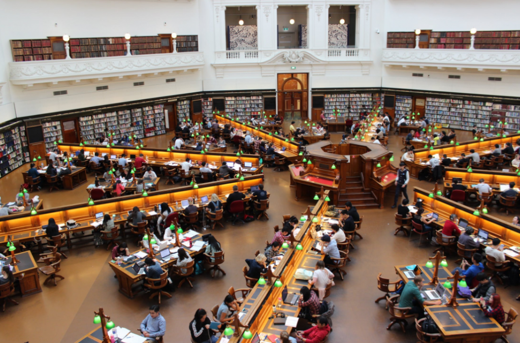 an overview of a huge library with a lot of students studying