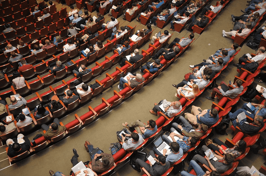 an overview photo of a group of people sitting on a room