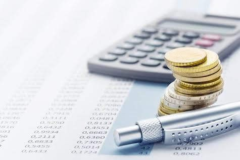 picture of coins, a pen, and calculator on top of a spreadsheet