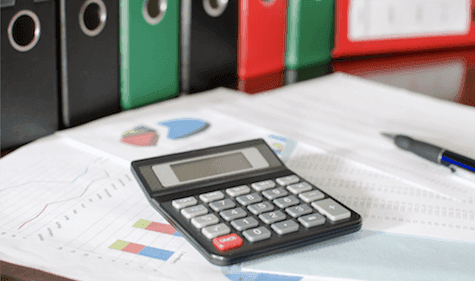 picture of calculator and pen on top of graphs and charts on papers