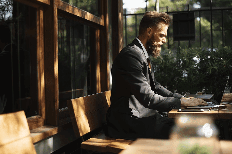 bearded man in a suit using his laptop on a cafe