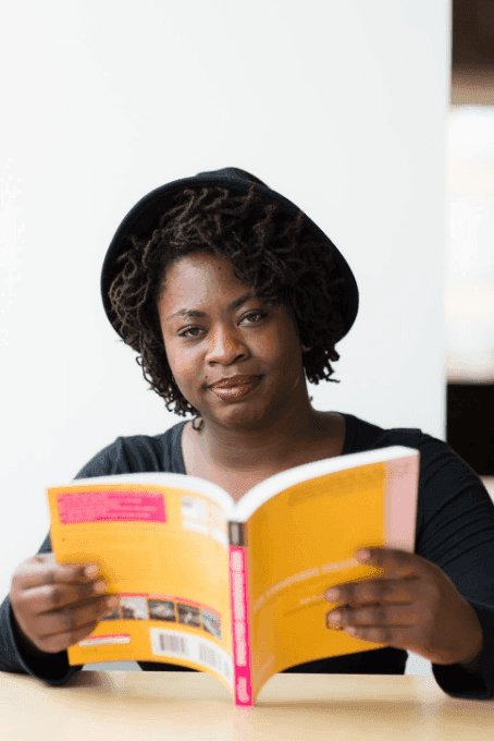 black woman holding a book looking at the camera