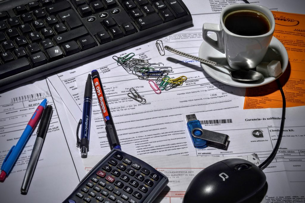 picture of a desk station with papers, coffee, pens, a calculator, usb and paper clips