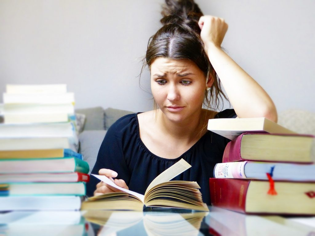 picture of a girl reading with a stressed out face and piles of books surrounding her