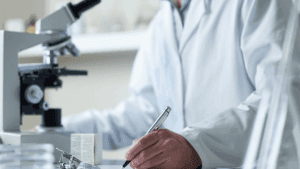 person in labcoat looking at microscope in a lab and writing notes