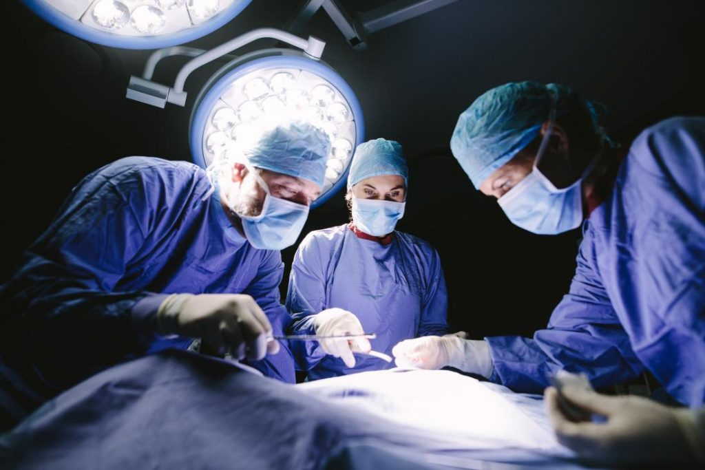 Image of three doctors performing surgery.