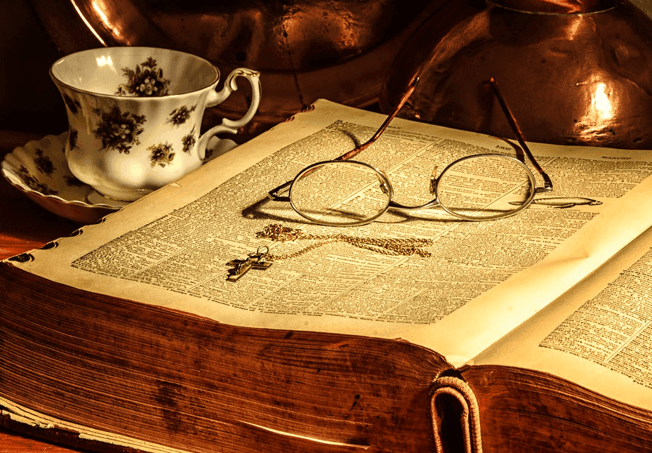 eyeglass on top of a huge book with a tea cup beside it