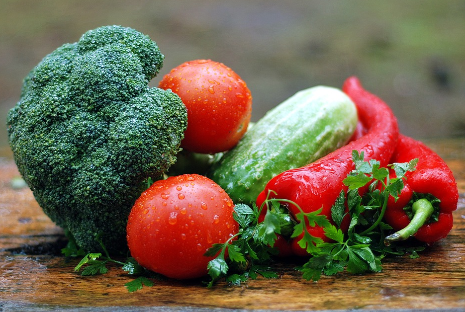 fresh vegetables including tomatoes, broccoli, and spices
