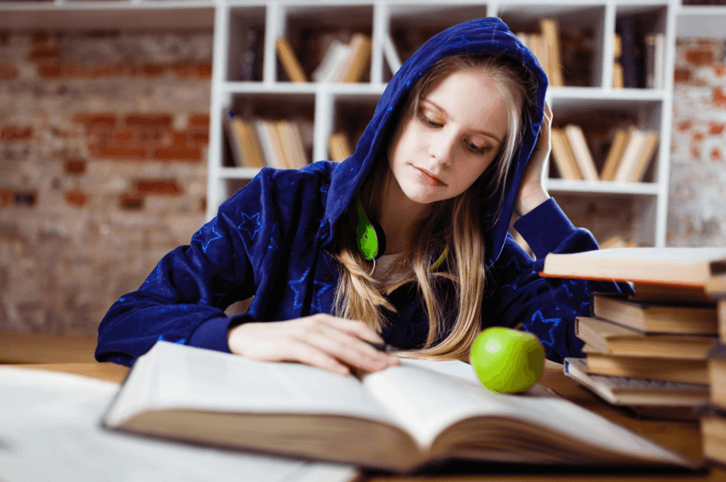 lady wearing a blue hoodie jacket, reading a book on the library