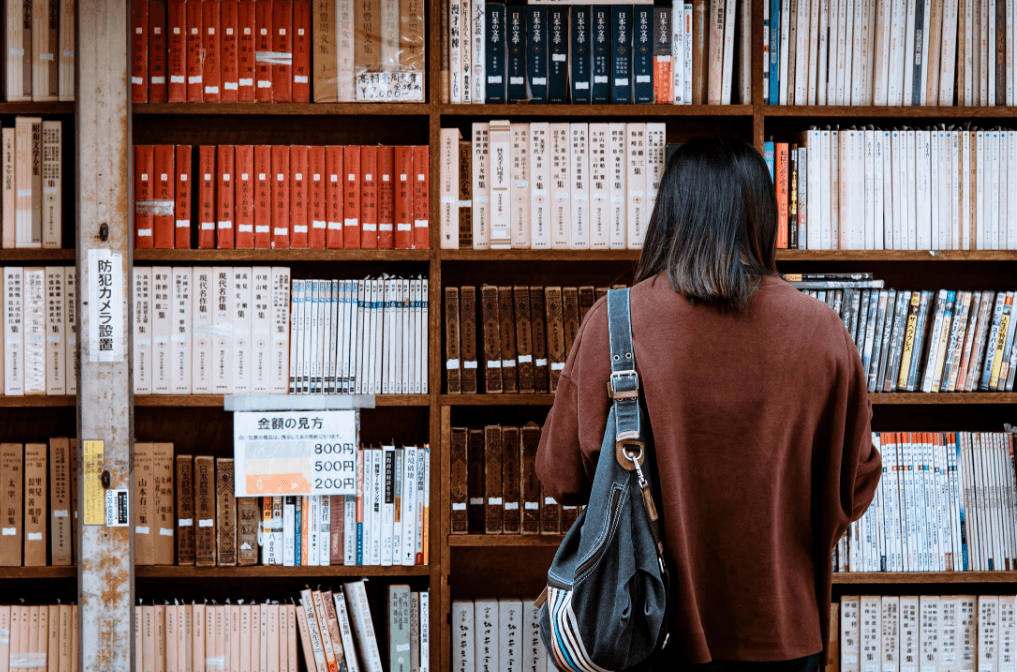 lady with a bag reading a book on a bookshelf