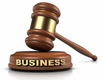 "A gavel sits atop a wood block with the word ""Business"" on it."