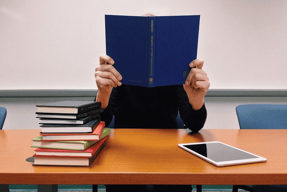 man holding a book beside a stack of books