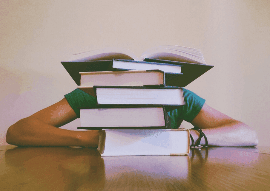 man sleeping in front of a pile of books