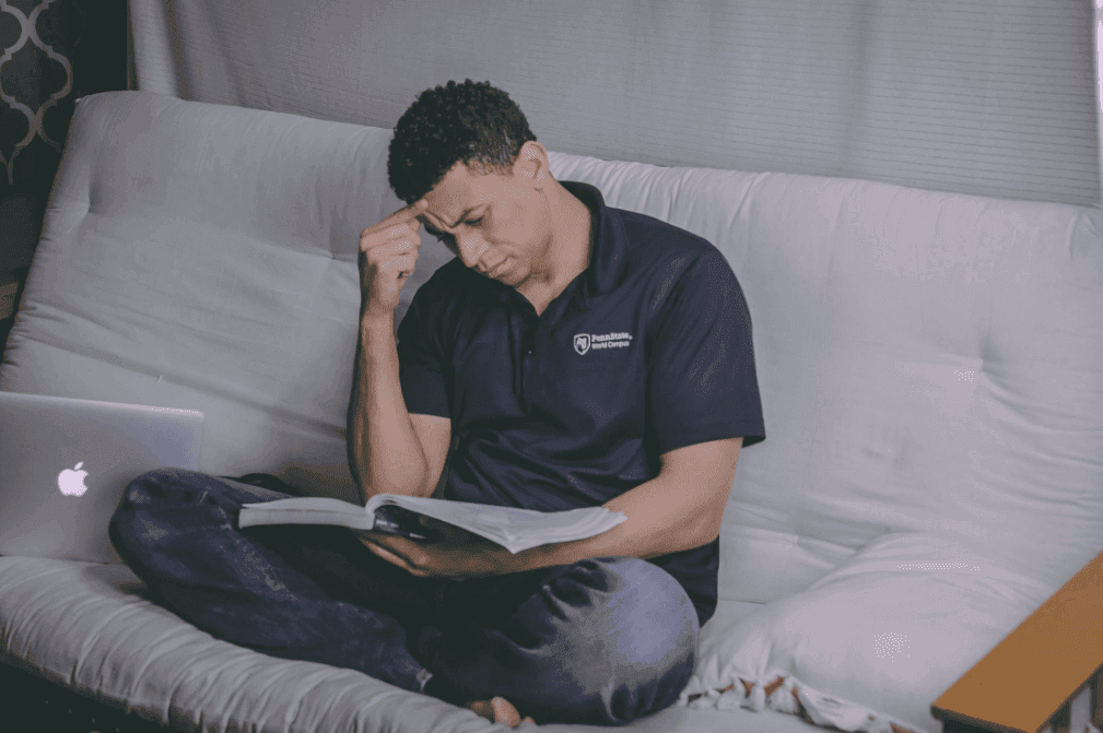 man thinking hard while reading a book on the couch