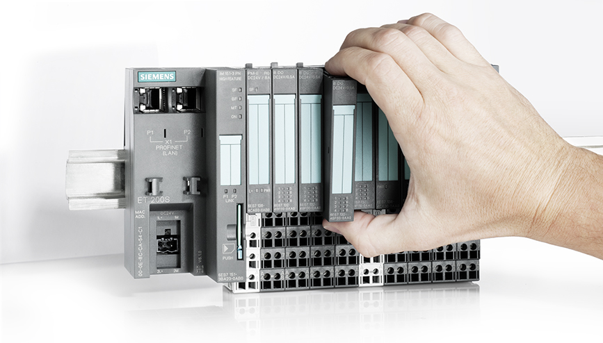A person's hand holding programmable logic controllers