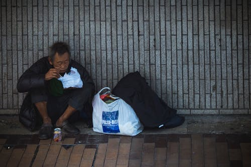 pictur of a homeless man sitting on the ground eating