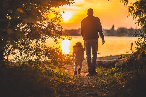 picture of a dad and his young daughter walking towards lake at sunset