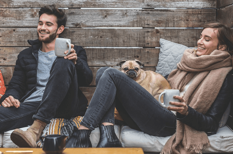 photo of a man and woman chilling while drinking coffee with a pug
