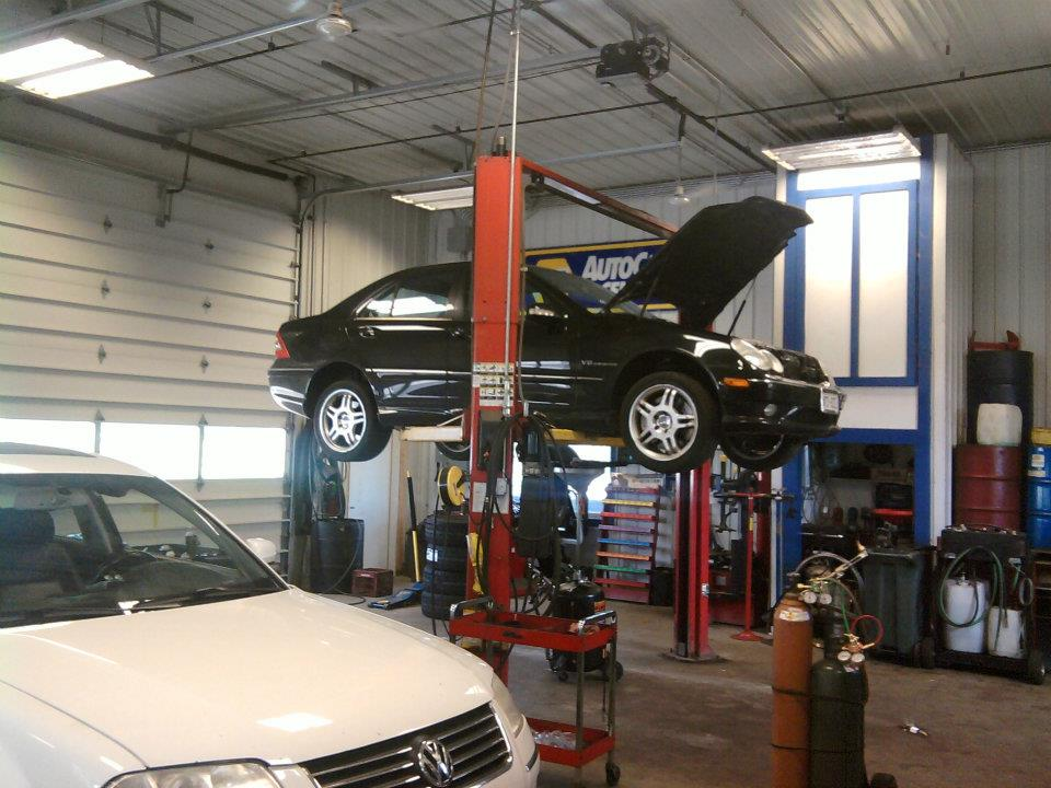 A worker safely lifts the car using hydraulics.