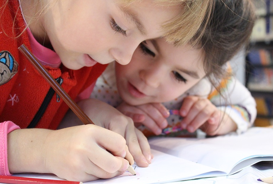 two young children writing on their artbook