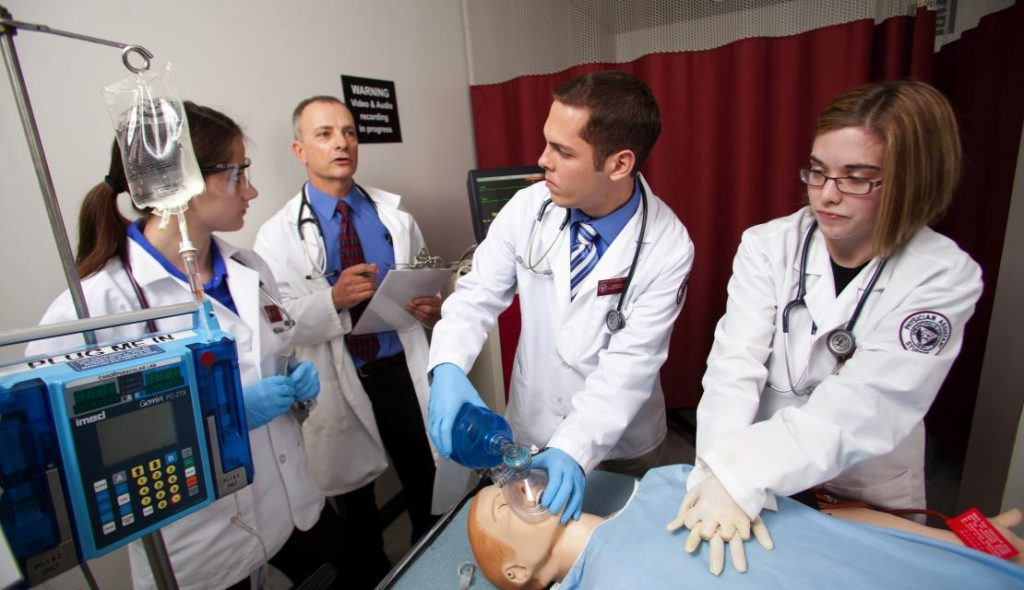 Student trainees learn how to perform CPR on a test dummy.