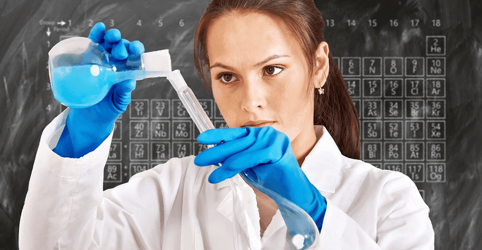 woman wearing a lab coat performing an experiment with test tubes