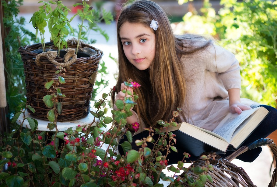 young girl holding a book while holding a flower