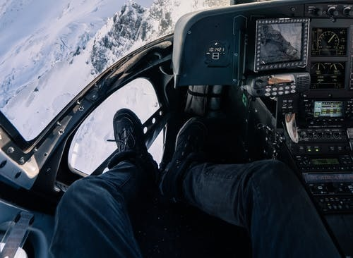 Picture of pilot in the cockpit with snowy mountains in view