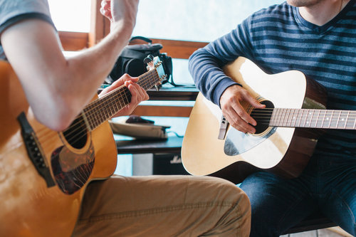Image of two people holding guitars and sitting across from each other.