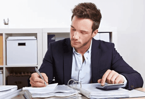 picture of businessman writing and calculating in open binder