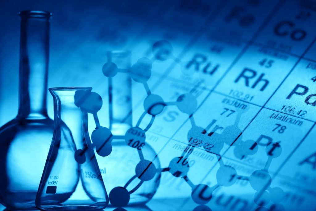 An image of beakers and molecules with the periodic table in the background