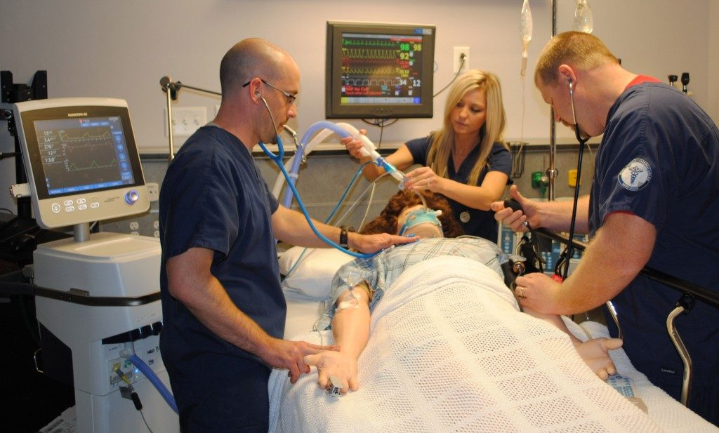 Doctors put a breathing mask over a patient.