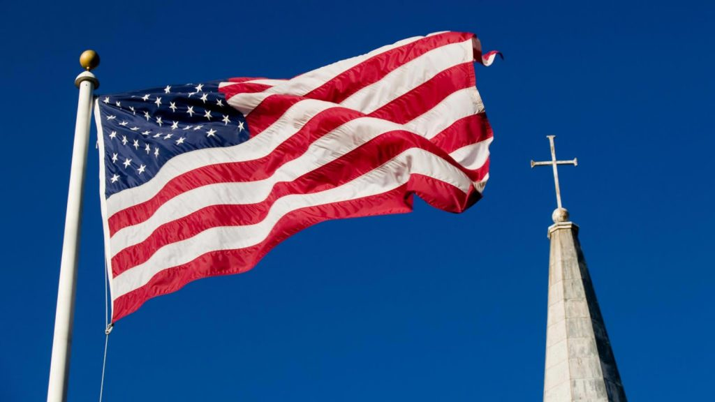 An American flag beside a Church's cross