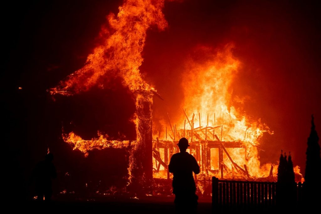 A house on fire with a silhouette of a firefighter standing in front of it