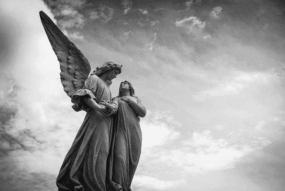 a statue of a woman and an angel in black and white