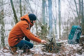 Picture of man making a fire in the wintertime, with a backback on the side