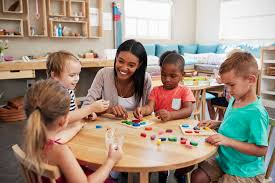 picture of a preschool setting with a teacher sitting at a table with 4 young kids