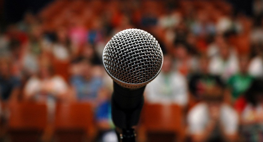 An image of a microphone on a stage in front of a large crowd of people