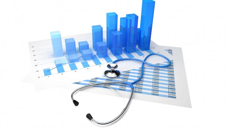 Image of a stethoscope sitting atop two pieces of paper, both with charts on them.