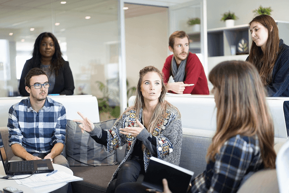 group of people talking with each other in a meeting