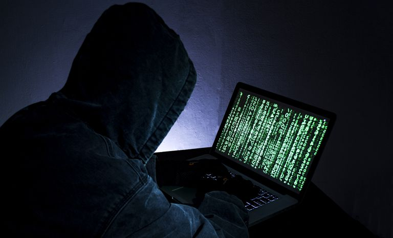 Someone in a black hoodie hacking a computer
