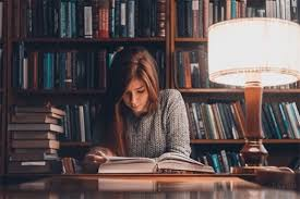 picture of girl in library reading books near a lamp