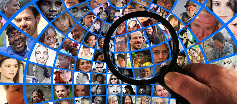 magnifying glass looking at pictures of people from various races