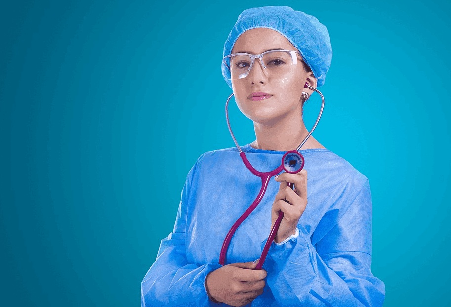 nurse wearing a lab gown and glasses and a stethoscope