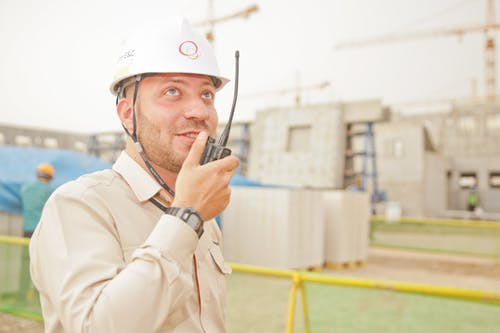 picture of an engineer talking in walkie-talkie with a hard hat on