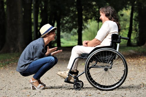 Picture of woman in wheelchair while another woman talks to her
