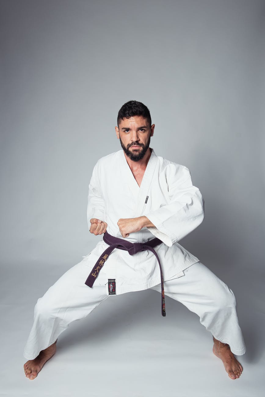 Picture of person with brown belt in a defense stance