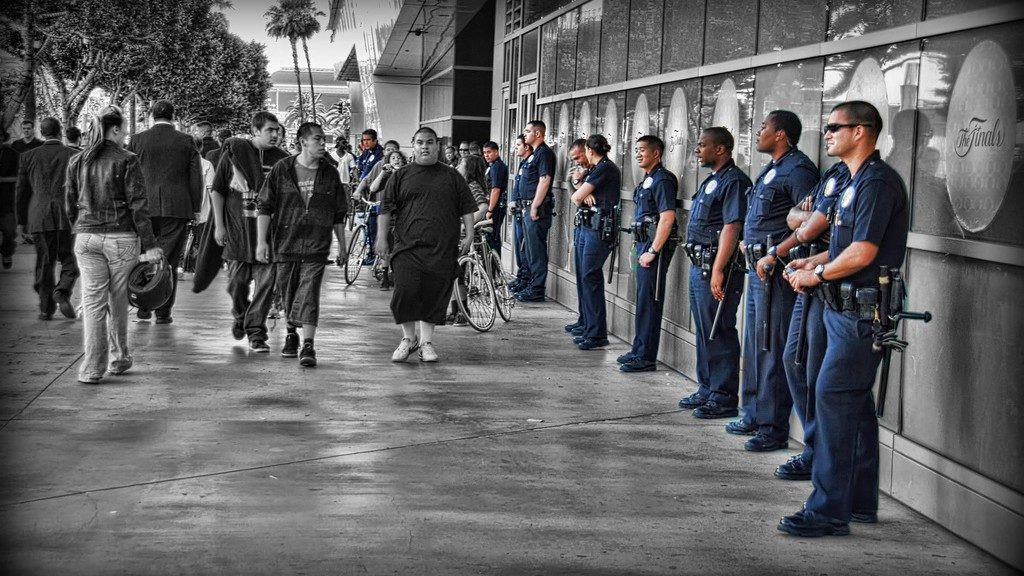 An image of policing, with police offers lined up on left in blue and the rest of the picture in black and white